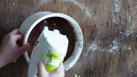 Visión superior que revuelve la pasta de la galleta del chocolate con el mezclador eléctrico en un cuenco plástico blanco metrajes