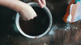 Visión superior que revuelve la pasta de la galleta del chocolate con una cuchara en un cuenco plástico blanco metrajes