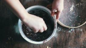 Visión superior que revuelve la pasta de la galleta del chocolate con una cuchara en un cuenco plástico blanco almacen de metraje de vídeo