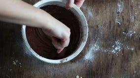 Visión superior que revuelve la pasta de la galleta del chocolate con una cuchara en un cuenco plástico blanco almacen de video