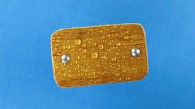 Visión superior, rotación del tablón de madera ligero con los pernos del hierro en gotas de agua Aislado almacen de video