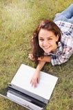 Visión superior si muchacha del estudiante que trabaja en el ordenador portátil, mintiendo en hierba en parque Foto de archivo