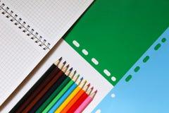 Visión superior sobre cuadernos, lápices, en un fondo azulverde De nuevo a concepto de la escuela foto de archivo