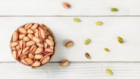 Visión tablero, pequeño cuenco con los pistachos turcos rojos, más nueces dispersadas en el escritorio del tablero blanco fotos de archivo libres de regalías