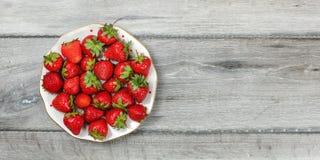 Visión tablero - placa con las fresas en el escritorio de madera gris, lugar para el texto en la derecha foto de archivo libre de regalías