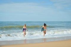 Visión trasera, amigas atléticas sanas de la persona que practica surf con los cuerpos del ajuste que llevan a cabo a tableros Imágenes de archivo libres de regalías