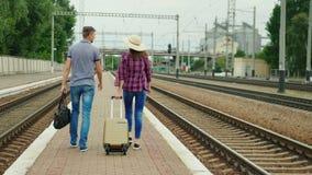 Visión trasera: Los pares felices jovenes de turistas con los bolsos del viaje van a lo largo del peron a lo largo del ferrocarri almacen de metraje de vídeo