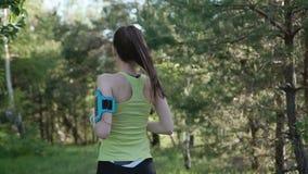 Visión trasera Mujer joven del corredor que corre en el parque que ejercita al aire libre tecnología usable del perseguidor de la almacen de video