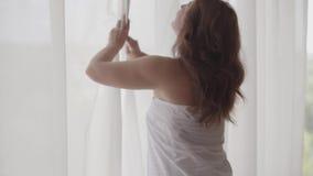 Visión trasera posterior en la situación madura rica del cordón de la cortina de abertura de la mujer en la mirada casera o moder almacen de metraje de vídeo