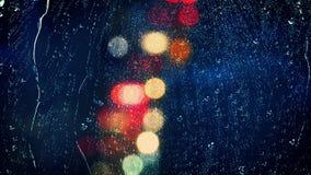 Visión a través de la ciudad lluviosa de la noche de la ventana almacen de metraje de vídeo
