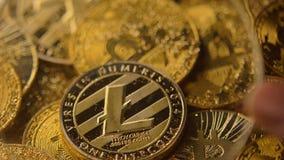 Visión a través de la lupa en el anverso de Litecoin en macro de la pila de las monedas almacen de metraje de vídeo