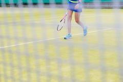 Visión a través de la red en las piernas del ` un s del jugador de tenis de la hembra Imagen de archivo