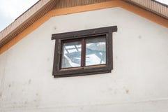 Visión a través de la ventana en la casa con la construcción dañada y derrumbada del tejado después del desastre natural de las c foto de archivo libre de regalías