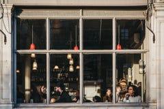 Visión a través de la ventana de la gente dentro del pub del café del mercado en el mercado de Broadway, Londres, Reino Unido imágenes de archivo libres de regalías