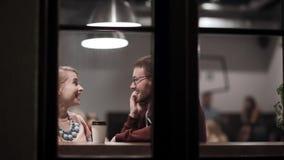 Visión a través de la ventana Pares jovenes que se sientan en el café, café de consumición, hablando, divirtiéndose junto en la t almacen de video