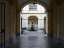 Visión a través de un arco de un patio formal Imagenes de archivo