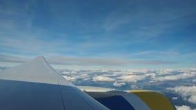 Visión a través de una ventana del aeroplano en el cielo y las nubes y la tierra del cielo a través de las nubes almacen de video