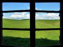 Visión a través de una ventana quebrada sobre prados Fotografía de archivo libre de regalías