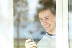 Visión a través de una ventana de un hombre que usa un teléfono elegante Foto de archivo