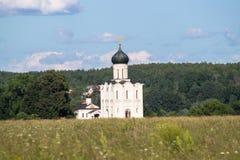 Visión a través del prado de Bogolubovo hacia la iglesia de la intercesión de la Virgen Santa en el río de Nerl Imagen de archivo libre de regalías