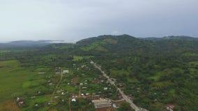 Visiónes increíbles desde arriba del pueblo y de las montañas grandes con el bosque verde almacen de metraje de vídeo