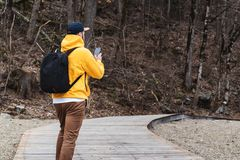 Visi?n posterior El turista del hombre en sudadera con capucha amarilla con la mochila se coloca al aire libre, usando smartphone imágenes de archivo libres de regalías