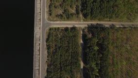 Visi?n superior desde el dron del bosque verde asombroso a la izquierda, del lago azul a la derecha, y del camino recto largo en  metrajes