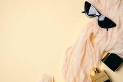 Visi?n superior, escritorio para mujer puesto plano Accesorios elegantes del inconformista, bufanda de seda, botella de perfume,  fotografía de archivo