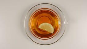 VISI?N SUPERIOR: La rebanada del lim?n nada en un t? negro en una taza de t? de cristal con un plato almacen de video