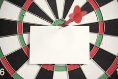 Visieren Sie roten Pfeil und Papieranmerkung über Mitte der Dartscheibe an Lizenzfreies Stockbild