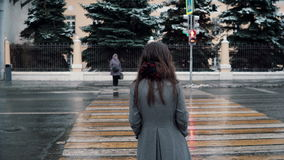 Visión posterior La muchacha morena joven triste está esperando la luz verde para cruzar el camino en una ciudad nevada del invie Foto de archivo libre de regalías