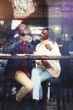Visión a través de la ventana de pares hermosos jovenes en café de consumición y la risa del amor mientras que se sienta en inter Foto de archivo libre de regalías