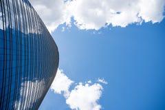 Visionärer Wolkenkratzer mit Hintergrund des blauen und bewölkten Himmels Lizenzfreie Stockfotos
