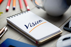 Vision  against notepad on desk Stock Photos