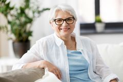 Portrait of happy senior woman in glasses at home. Vision, age and people concept - portrait of happy senior woman in glasses sittin on sofa at home stock photos
