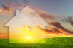 Vision av ett nytt hus på grönt fält på solnedgången för delshus för gods försäljning för hyra verklig arkivfoton