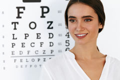 Vision. Beautiful Woman With Visual Eye Test Chart On Background. Optometry And Vision. Portrait Of Beautiful Smiling Girl Face At Opthalmologist Office. Closeup Stock Photo