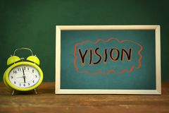 Vision on board. Vision text on board and clock on wooden table stock photos
