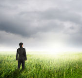 Vision business man in fields and rainclouds Stock Images