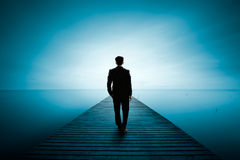 Vision. Busness man standing on wooden bridge and looks at the sea stock image