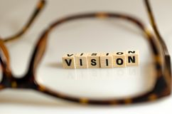 Vision. Clearer vision with glasses.the word vision written in cubes Royalty Free Stock Photography