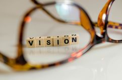 Vision. Clearer vision with glasses.the word vision written in cubes Royalty Free Stock Photo