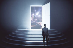 Vision concept. Back view of young man looking at night city through open door in concrete interior with steps. Vision concept. 3D Rendering Royalty Free Stock Photos