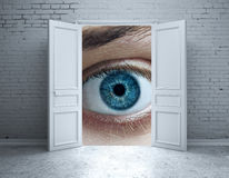 Vision concept. Brick interior with open door and abstract blue eye. Vision concept Royalty Free Stock Photos