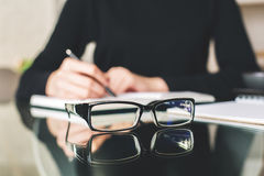 Vision concept. Close up of spectacles placed on glass table. Blurry woman in the background writing in notepad. Vision concept Stock Photography