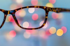 Vision concept glasses. Eyeglasses against bokeh Christmas lights background. Vision or business concept Stock Photography