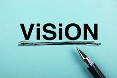 Vision concept. Vision text is on blue paper with black ball-point pen aside Stock Images
