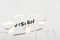 Vision concept. Vision word written on a piece of puzzle over group of paper jigsaw puzzles Royalty Free Stock Photo
