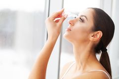 Vision concept. Young Beautiful Woman With Eyedrops.  royalty free stock photography