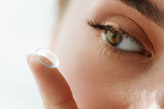 Vision Contact Lenses. Closeup With Beautiful Woman Face. Contact Lens For Vision. Closeup Of Female Eye With Applying Contact Lens On Her Brown Eyes. Beautiful Royalty Free Stock Photography